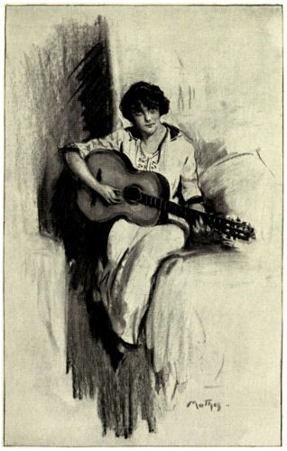 Helena sits playing a guitar